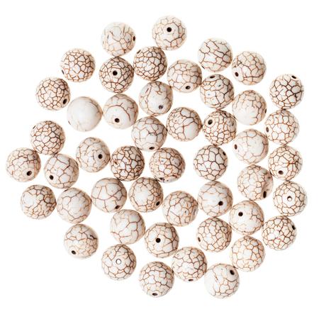 opal: many beads from cracked cacholong (milky white opal) gemstone on white background