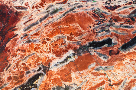 tumbled stones: natural background - texture of red brecciated jasper mineral gem stone close up