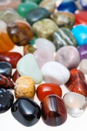 tumbled: many polished natural mineral gemstones close up on white background