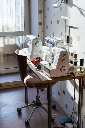 sewing machines: workplace of seamstress at home - sewing machines and serger on table Stock Photo