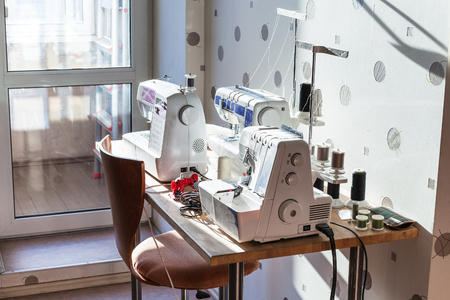 sewing machines: workshop of seamstress at home - sewing machines and serger on table Stock Photo