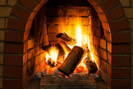 firebox: burning billets in fire-box of fireplace in country cottage