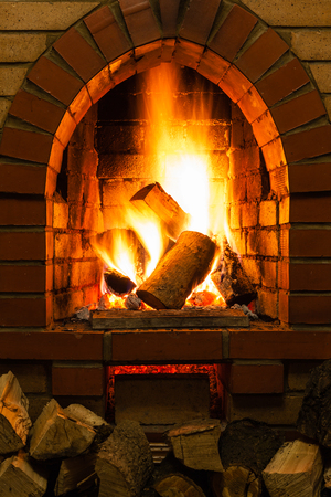 firebox: firewood and fire in fireplace in country cottage Stock Photo