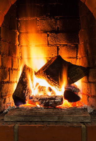 firebox: burning firewood in fire-box of fireplace in country cottage