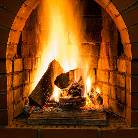 open country: open fire in fire-box of brick fireplace in country cottage