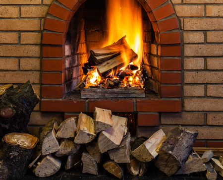 firebox: stack of wood and burning wood in indoor brick fireplace in country cottage
