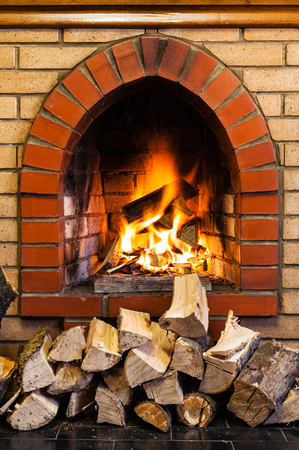 fire brick: stack of wood and fire in indoor brick fireplace in country cottage Stock Photo
