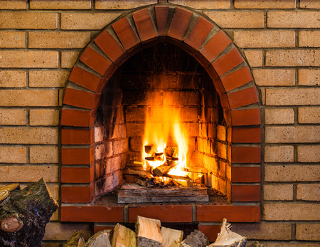 open country: open fire in indoor brick fireplace in country cottage