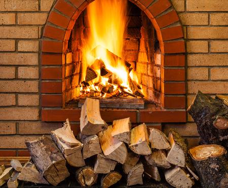pile de bois de chauffage et le feu dans une cheminée en briques couverte en chalet Banque d'images