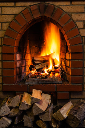 firebox: wood stack and logs burning in indoor brick fireplace in country cottage