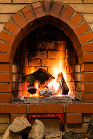 firebox: few wood and burnuing logs fire in fireplace in country cottage Stock Photo