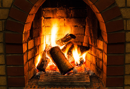 firebox: burning wooden logs in fire-box of fireplace in country cottage Stock Photo