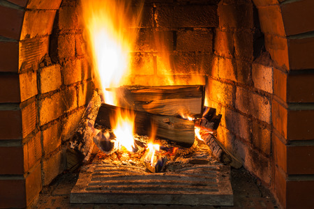 firebox: burning wood in brick fireplace in country cottage