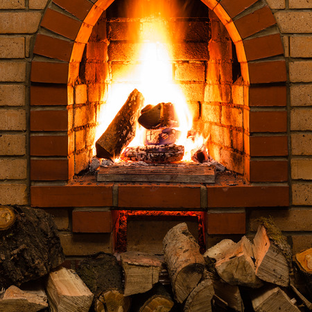 firebox: stack of wood and tongues of fire in indoor brick fireplace in country cottage