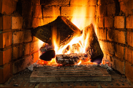 firebox: burning wood in fire-box of fireplace in country cottage