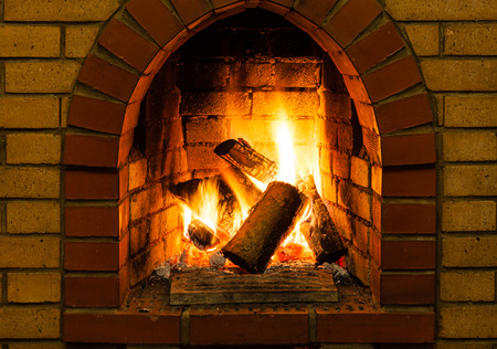 hearth and home: burning wooden logs in brick fireplace in country cottage