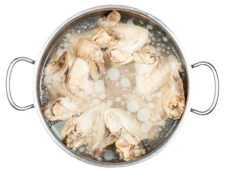greasy: stewpan with cold boiled chicken wings in frozen greasy chicken bouillon isolated on white background