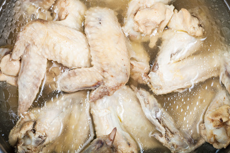 greasy: many boiled chicken wings in greasy chicken bouillon in stewpan Stock Photo