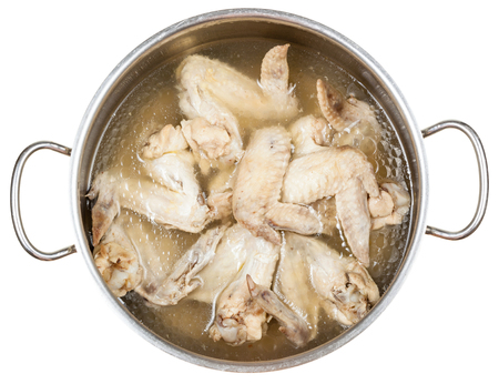 greasy: stewpan with boiled chicken wings in greasy chicken bouillon isolated on white background Stock Photo
