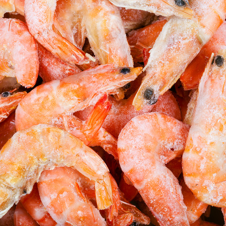 close up food: food square background - frozen boiled red shrimps close up