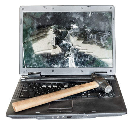 snapped: direct view of old broken laptop with hammer on keyboard isolated on white background