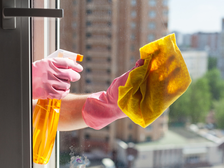 window washer: washing home window - washer washes window glass with detergent in apartment house