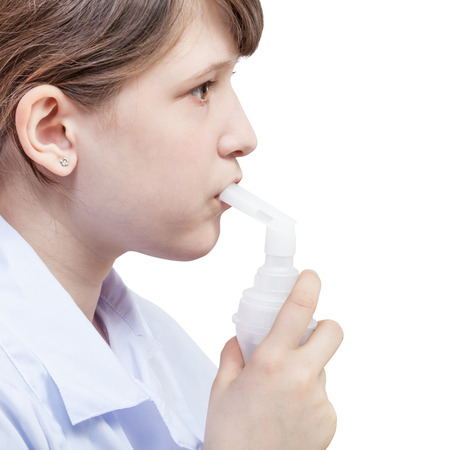 inhaled: medical inhalation treatment - girl inhales with mouthpiece of modern jet nebulizer isolated on white background