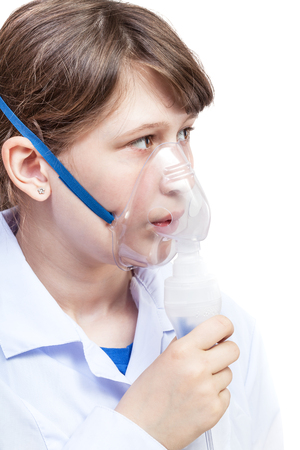inhaled: medical inhalation treatment - girl breathes with face mask of modern jet nebulizer isolated on white background