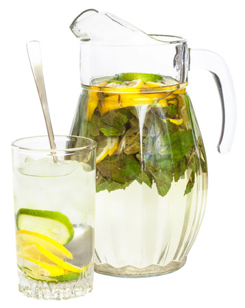 tumbler: side view of glass pitcher and tumbler with natural lemonade drink from lemon, lime, mint isolated on white background Stock Photo