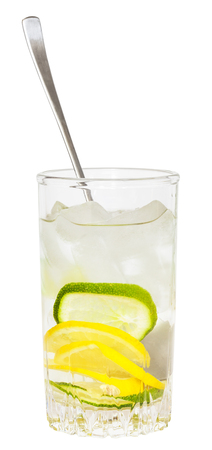tumbler: glass tumbler with spoon and cold lemonade drink from lemon and lime isolated on white background