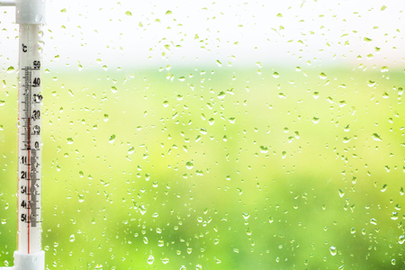 pane: green background - raindrops on window pane and thermometer in summer day