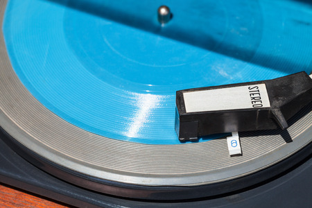 flexi: above view of headshell of old turntable on blue flexi disc