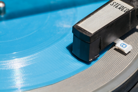 flexi: headshell of old turntable on blue flexi disc close up