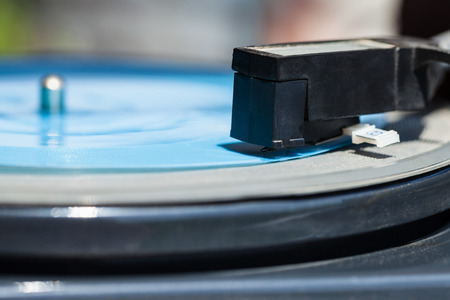 flexi: side view of headshell with stylus of turntable on blue flexi disc