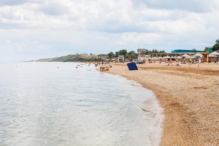 kuban: GOLUBITSKAYA, RUSSIA - JULY 21, 2016: tourists on sand and shelly beach Sea of Azov, Temryuk bay in Golubitskaya resort, Kuban. Golubitskaya is very popular holiday destination on the Taman peninsula