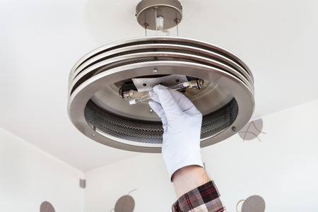 halogen: Electrician mounts halogen lamp in ceiling light in room
