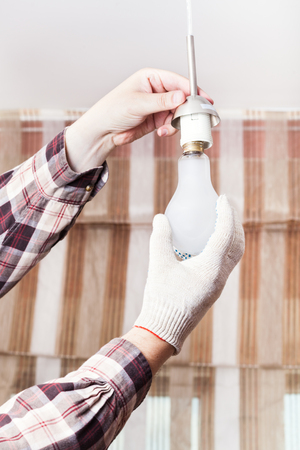 replace: Electrician replace incandescent lamp in lampholder in room Stock Photo
