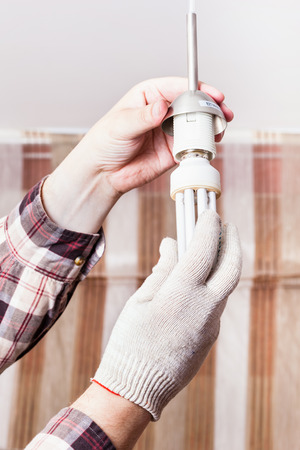 downlight: Electrician changing compact fluorescent lamp in lampholder in room