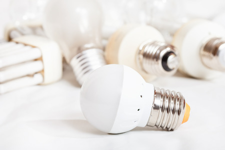 energy saving new LED lamp and many old incandescent light bulbs and used compact Fluorescent lamps Stock Photo
