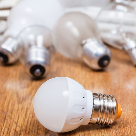new LED lamp and old incandescent light bulbs and used compact Fluorescent lamps on table