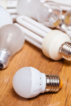 energy saving LED lamp and pile of old incandescent light bulbs and used compact Fluorescent lamps on wooden board