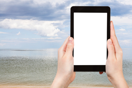 azov: travel concept - tourist photographs of view of Azov Sea on tablet pc with cut out screen with blank place for advertising