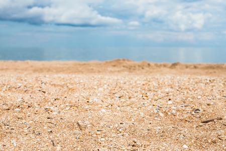 foreground focus: Foreground focus - sand and shelly beach close up and white clouds over blue sea. Coasline of Sea of Azov, Temryuk bay, Golubitskaya resort, Taman peninsula, Kuban, Russia Stock Photo