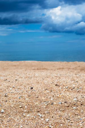 foreground focus: Foreground focus - shelly and sand beach close up and dark blue rain clouds over sea. Coastline of Sea of Azov, Temryuk bay, Golubitskaya resort, Taman peninsula, Kuban, Russia