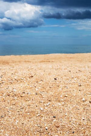 foreground focus: Foreground focus - surface of shelly and sand beach close up and dark blue rain clouds over sea. Coastline of Sea of Azov, Temryuk bay, Golubitskaya resort, Taman peninsula, Kuban, Russia