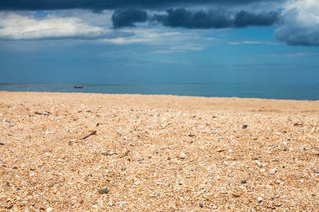 foreground focus: Foreground focus - scenery with sand beach and dark blue rain clouds over sea. Coastline of Sea of Azov, Temryuk bay, Golubitskaya resort, Taman peninsula, Kuban, Russia