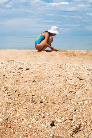 foreground focus: sand and shelly beach close up with blurred playing girl and sea on background. Foreground focus. Coastline of Sea of Azov, Temryuk bay, Golubitskaya resort, Taman peninsula, Kuban, Russia