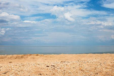 foreground focus: Foreground focus - sand and shelly beach and white clouds over sea. Coastline of Sea of Azov, Temryuk bay, Golubitskaya resort, Taman peninsula, Kuban, Russia