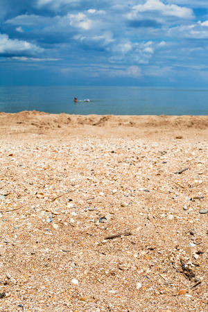 foreground focus: Foreground focus - sand and shelly beach close up and dark blue sea. Coastline of Sea of Azov, Temryuk bay, Golubitskaya resort, Taman peninsula, Kuban, Russia