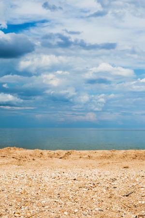 foreground focus: Foreground focus - sand and shelly beach and dark blue clouds over sea. Coastline of Sea of Azov, Temryuk bay, Golubitskaya resort, Taman peninsula, Kuban, Russia